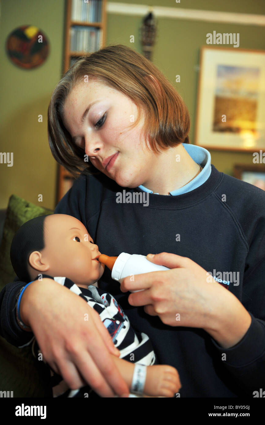 A 13 year old girl minds a 'real care baby' for the weekend as part of a school project to prevent teenage - Stock Image