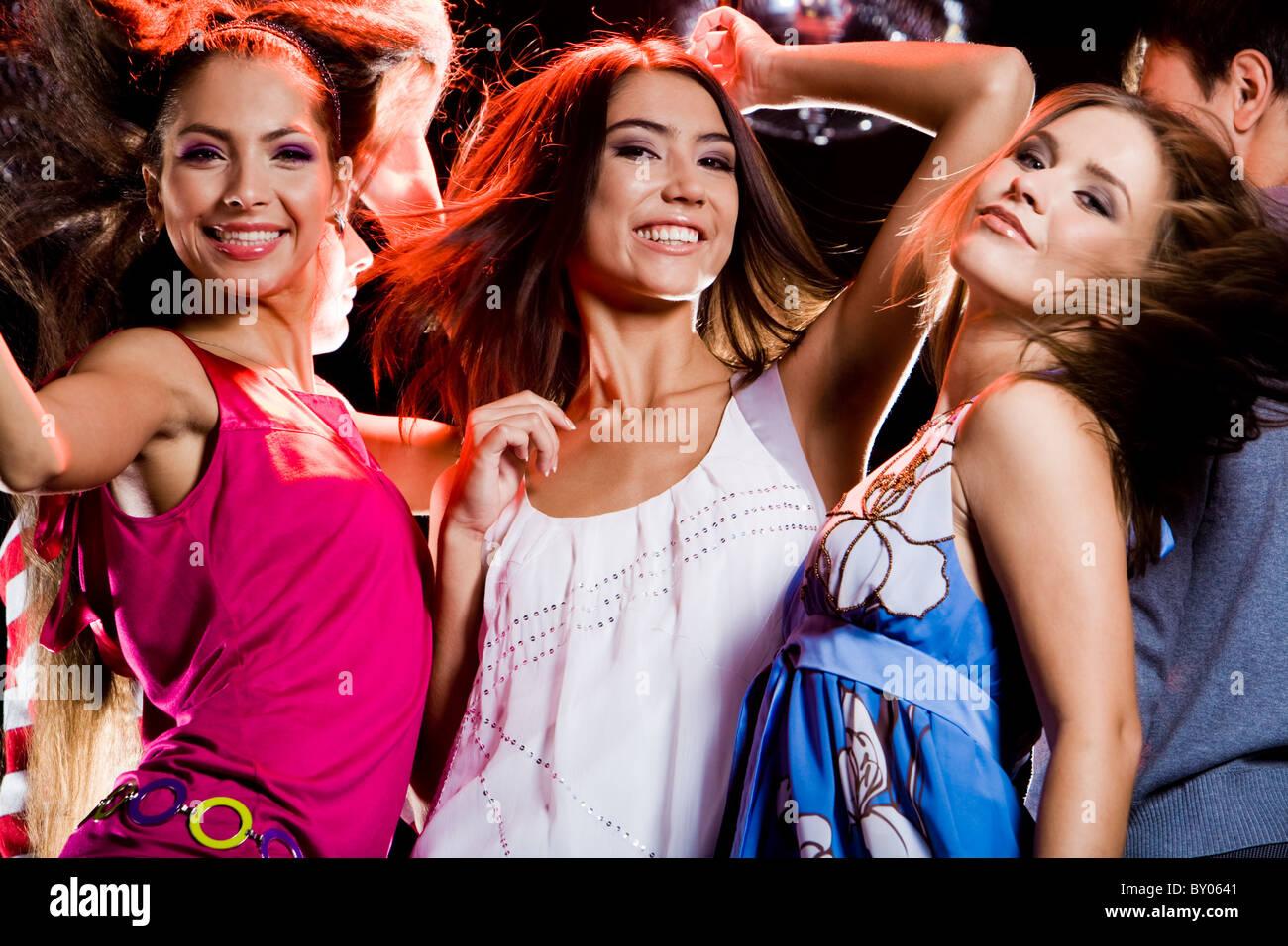 Three glamorous girls having fun at disco in night club - Stock Image