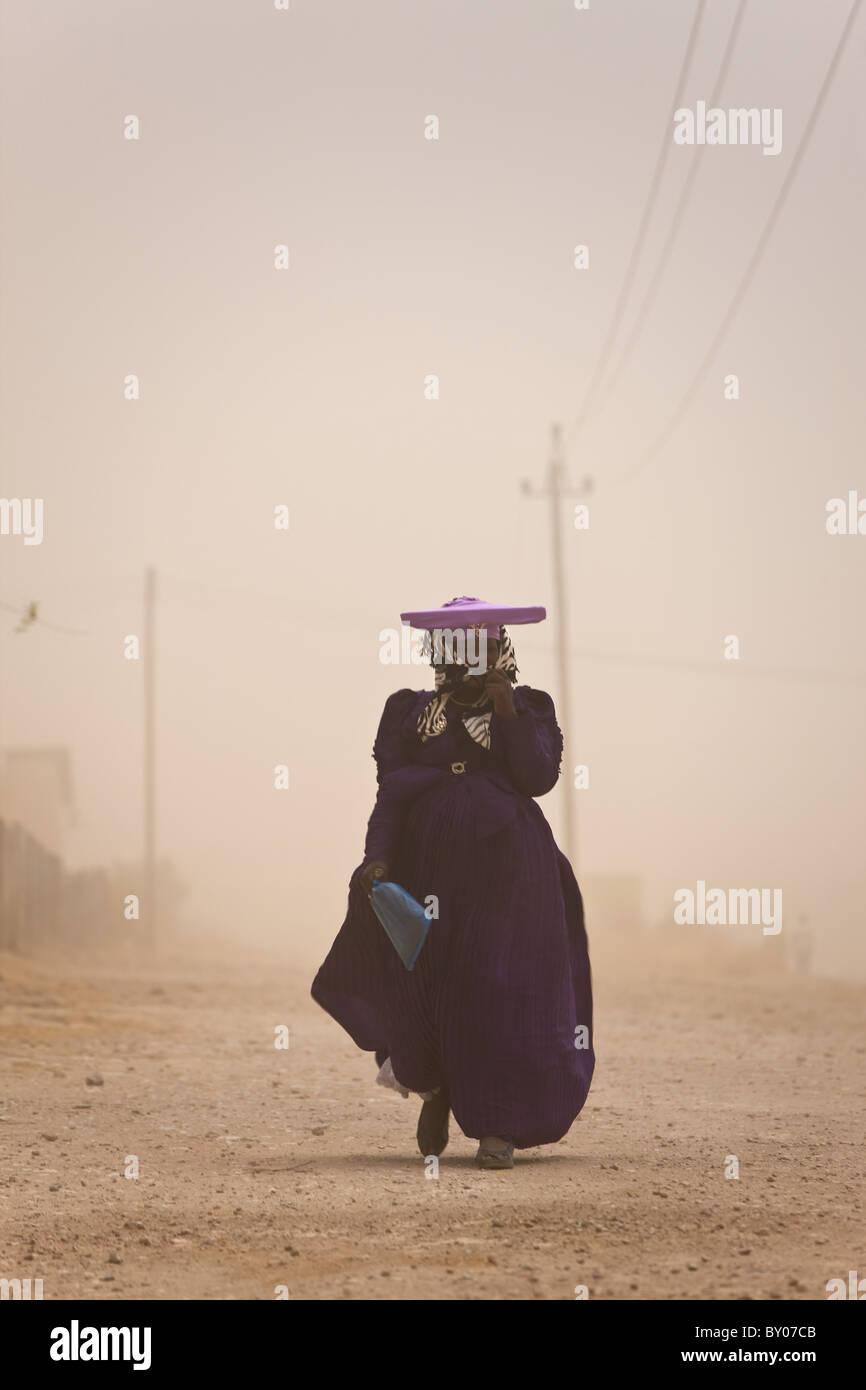 Herero woman in dust storm, Opuwo, Namibia - Stock Image