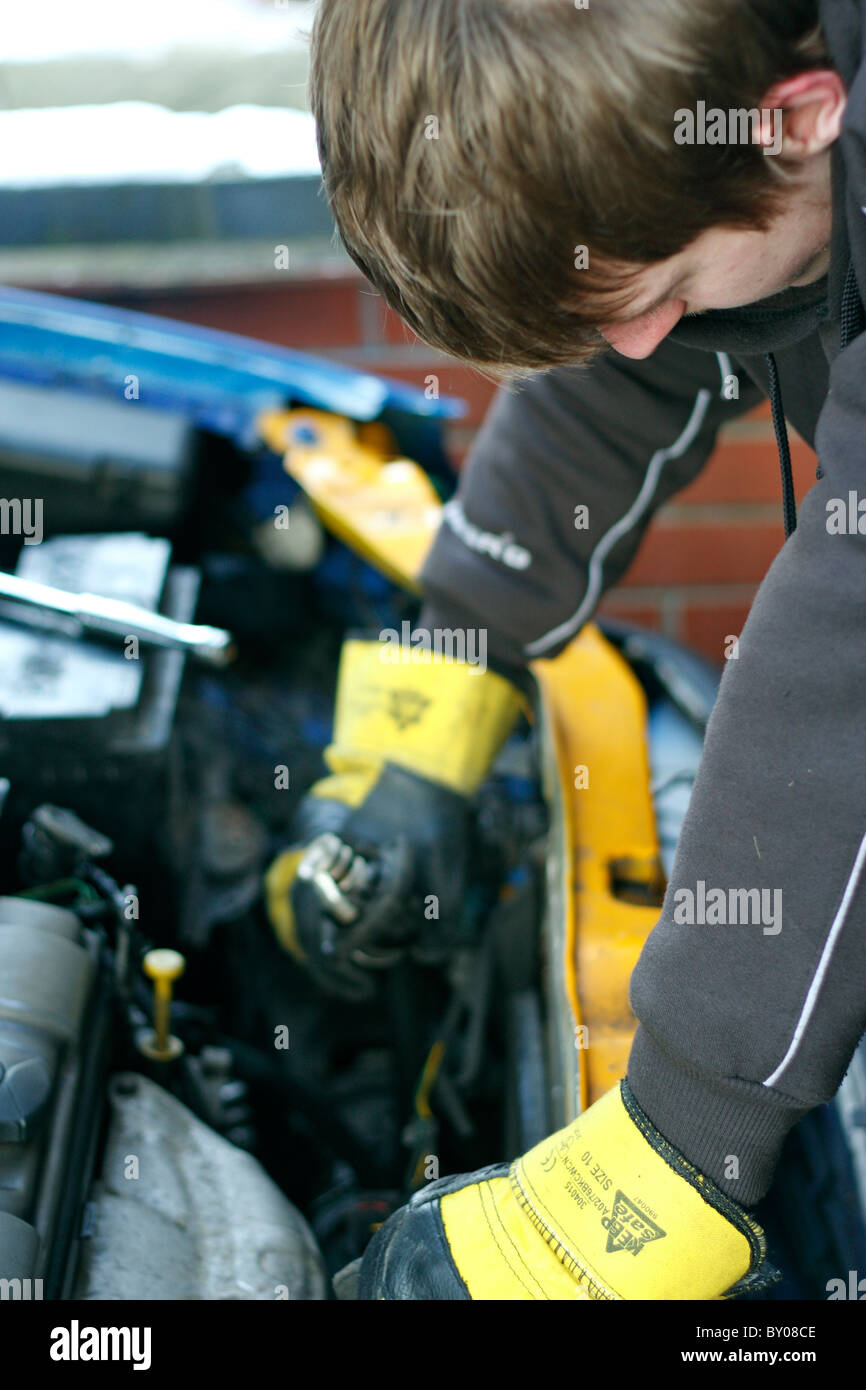A young Caucasian male mechanic working under the bonnet of a car, wearing protective gloves. - Stock Image