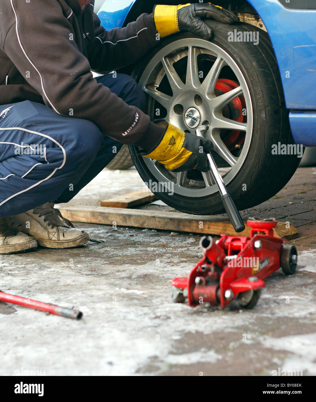A mechanic unscrewing the wheel nuts with a wrench to remove the wheel from a car, wearing rigger gloves for protection. - Stock Image