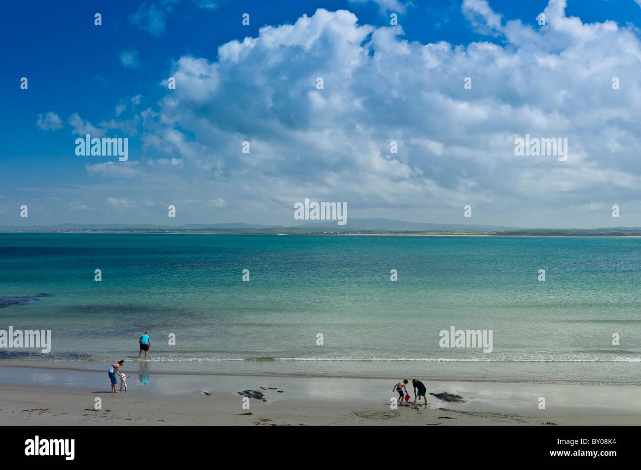 Family fun at the sandy beach on the west coast near Doonbeg, County Clare, West Coast of Ireland - Stock Image