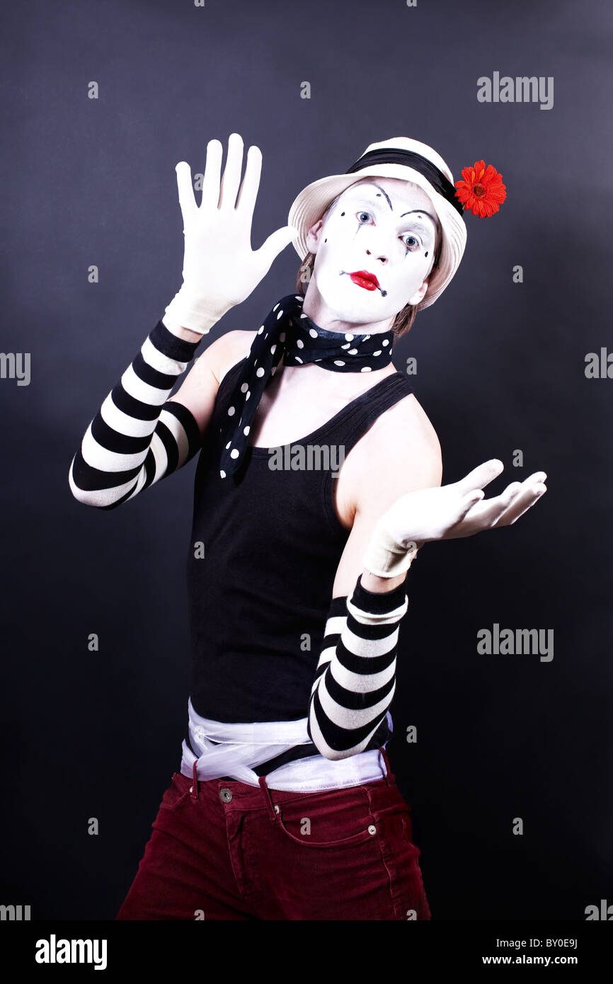 Theatrical mime in white hat with red flower on black background - Stock Image