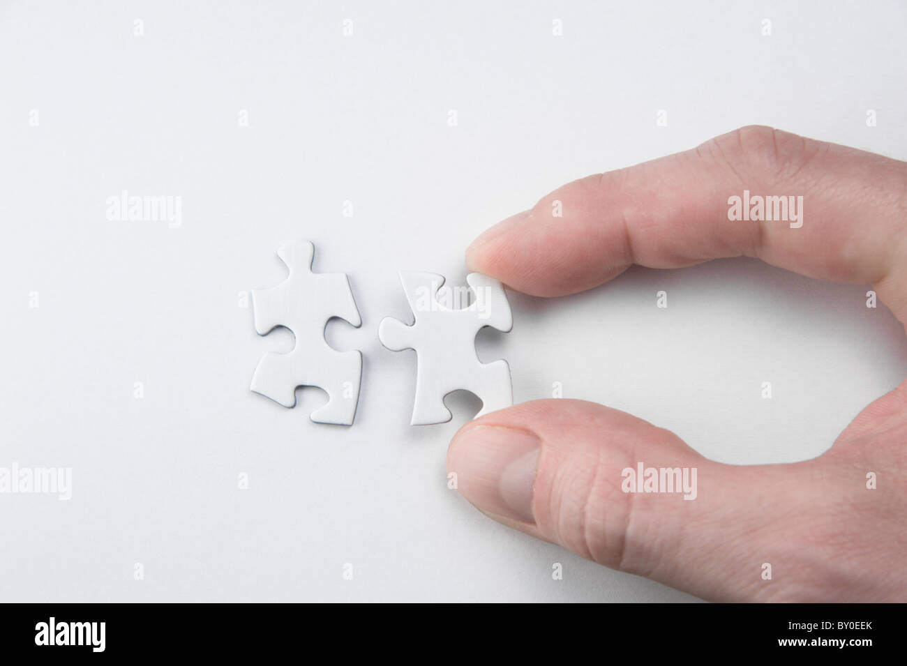 A hand, connecting two pieces of a puzzle - Stock Image