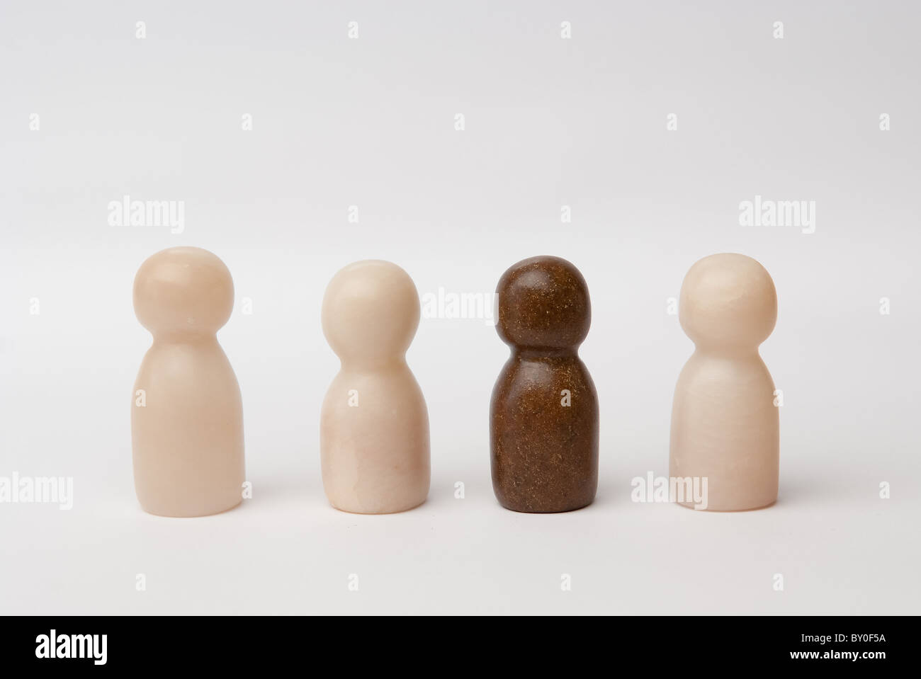 3 white and 1 brown figure - Stock Image