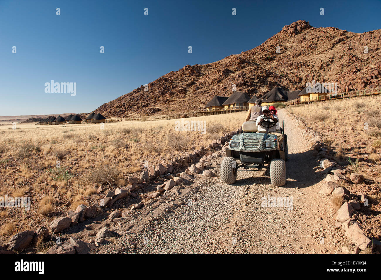 Sossus Dune Lodge within Namib-Naukluft Park in central Namibia.  Rugged golf carts transfer visitors between vehicles - Stock Image