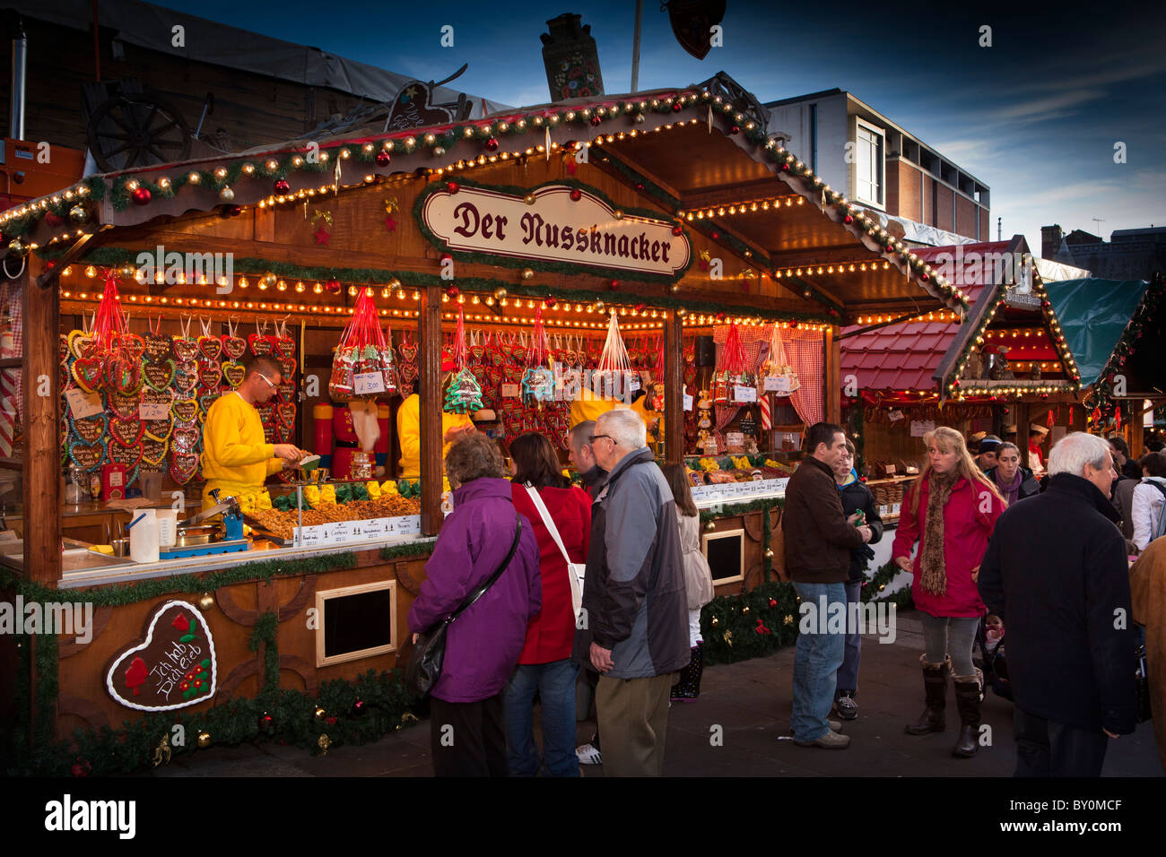 UK, England, Yorkshire, Leeds, Milennium Square, Christkindelmarkt, shoppers browsing confectionery stall - Stock Image