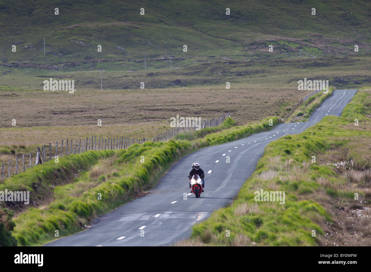 Motorcyclist on Kylemore Pass in Connemara National Park, County Galway, Ireland - Stock Image