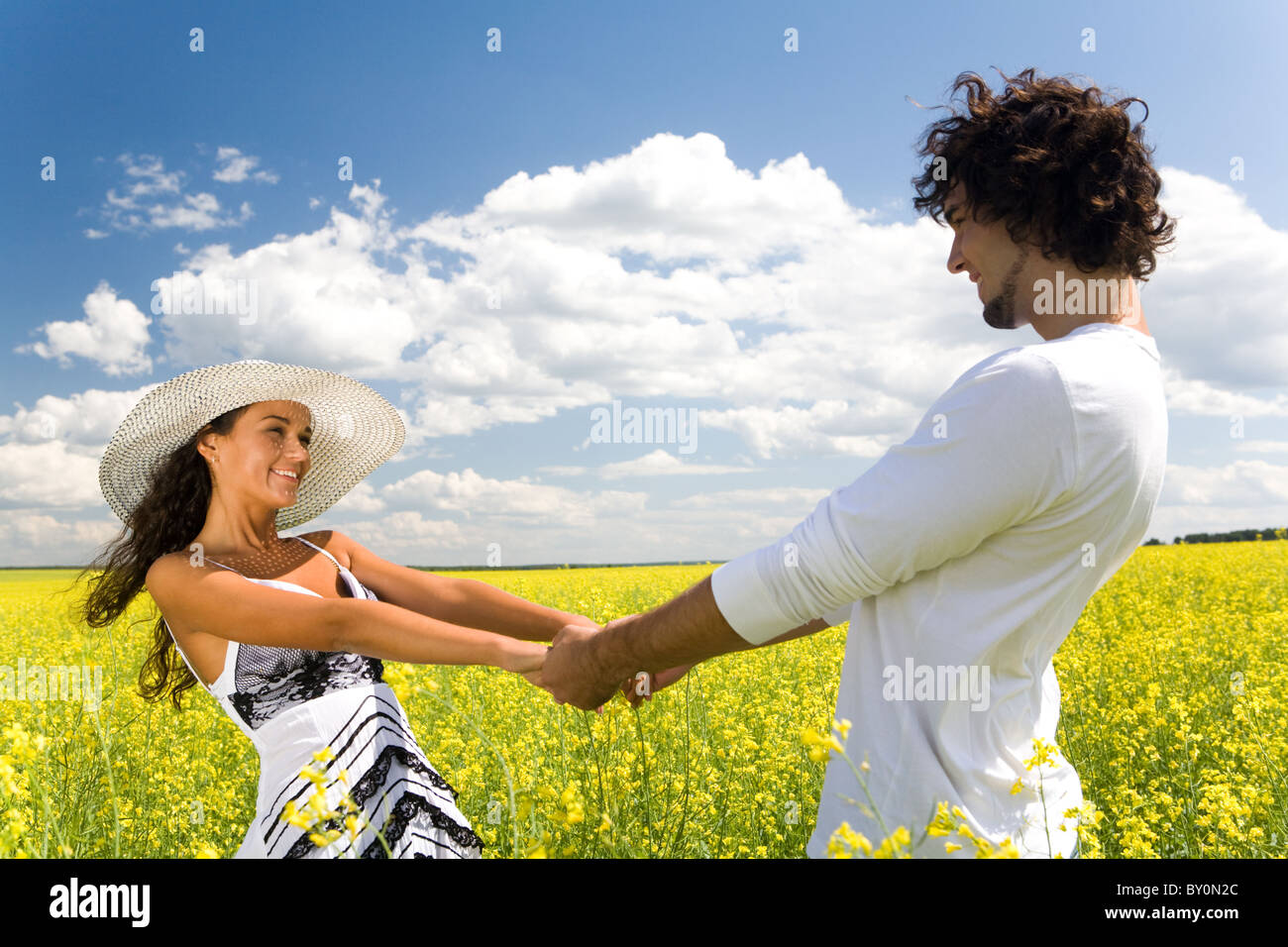 Photo of attractive couple holding by hands and whirling on the meadow at leisure - Stock Image