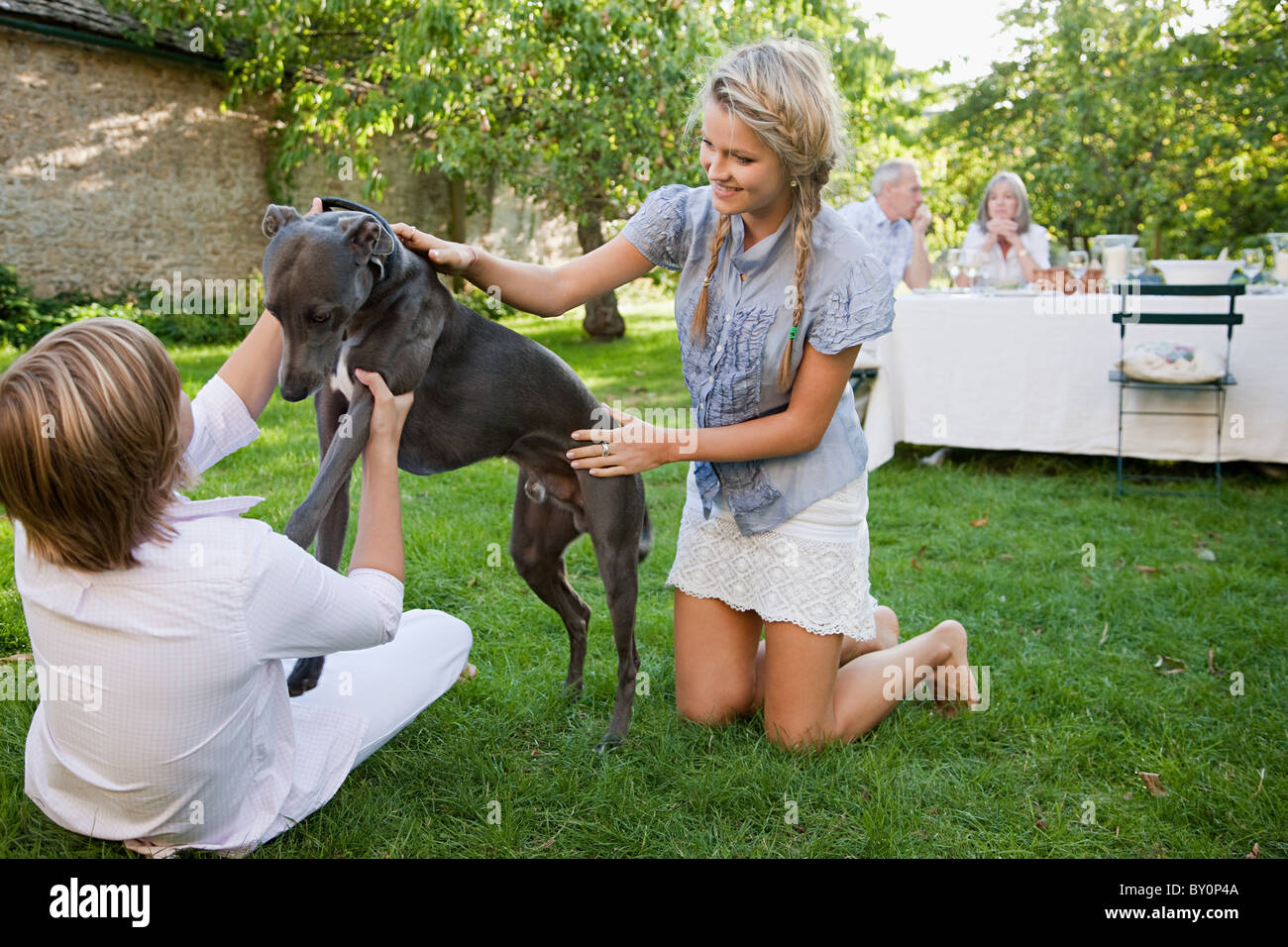 Brother and sister playing with pet dog - Stock Image