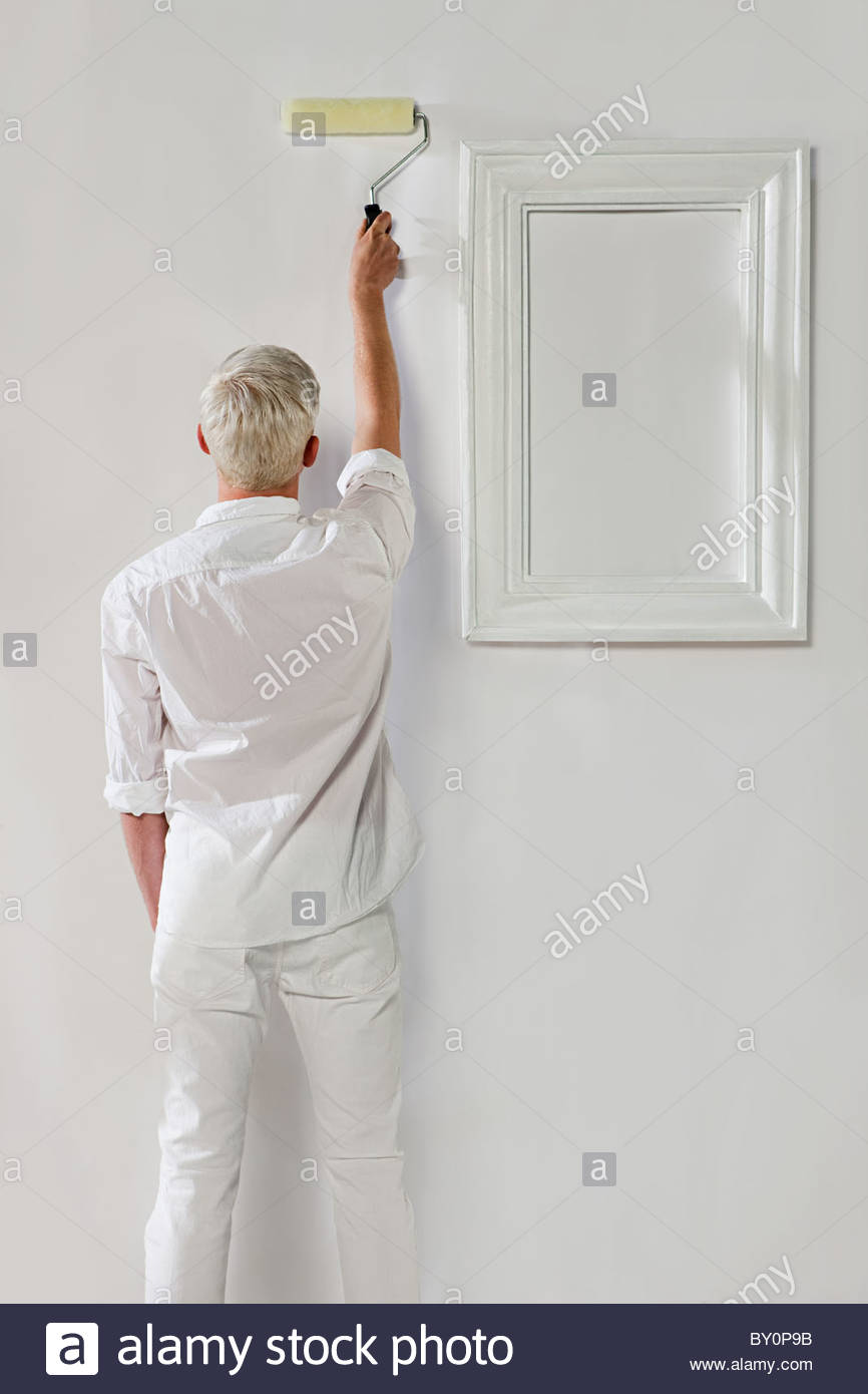 Young man using paint roller on white wall with picture frame - Stock Image