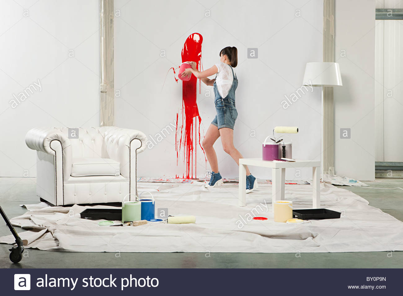 Young woman splashing red paint on white wall - Stock Image