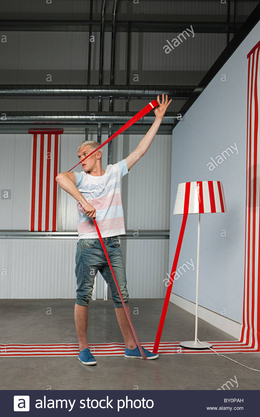Young man getting stuck on red adhesive tape - Stock Image