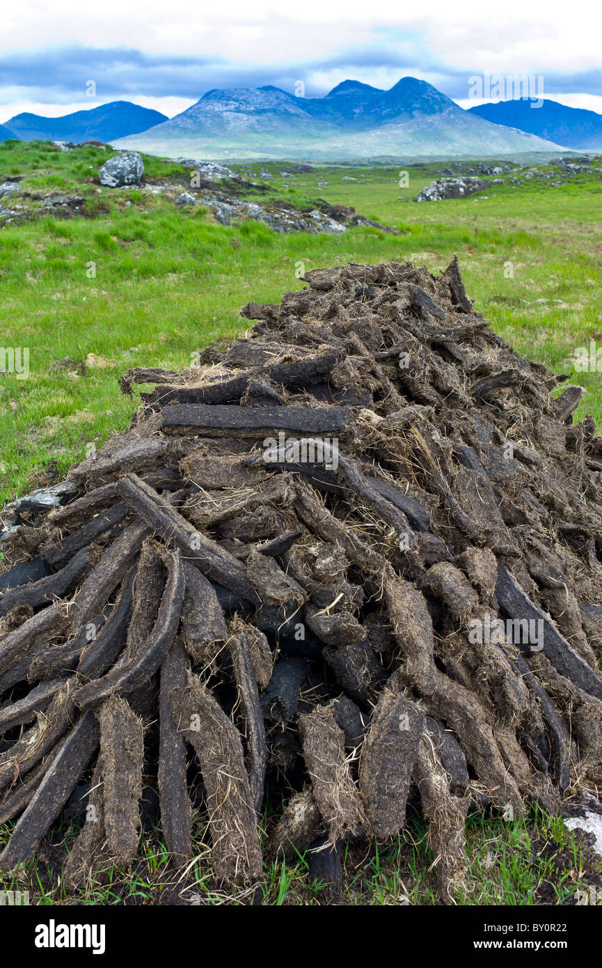 Stacked peat in turf bog on the Old Bog Road near Roundstone, Connemara, County Galway - Stock Image