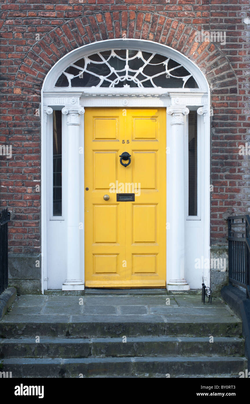 A yellow front door belonging to one of the Georgian buildings on O'Connell street in Limerick, Republic of Ireland. Stock Photo