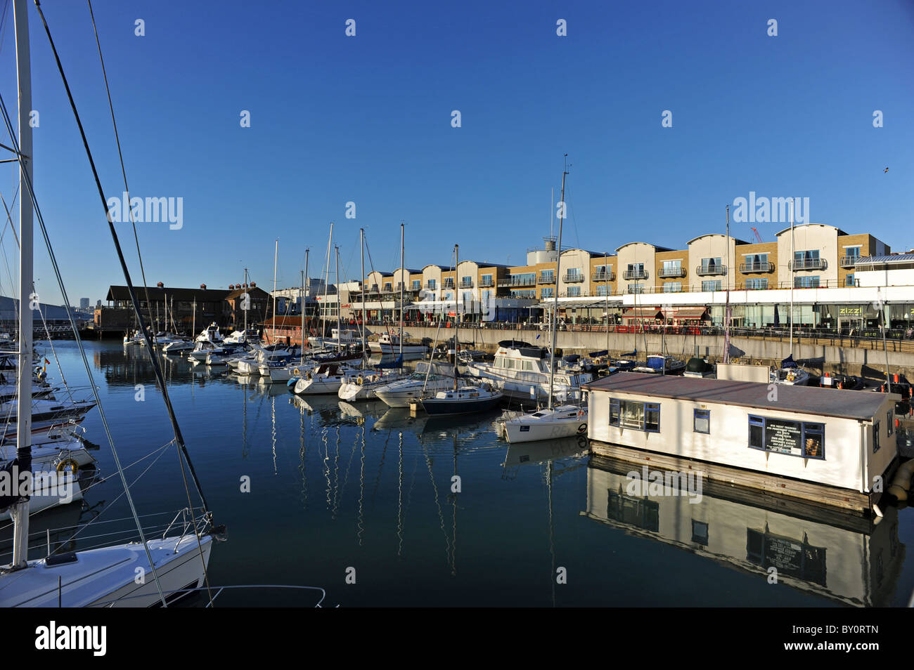 Boats moored in Brighton Marina as the sun starts to set - Stock Image