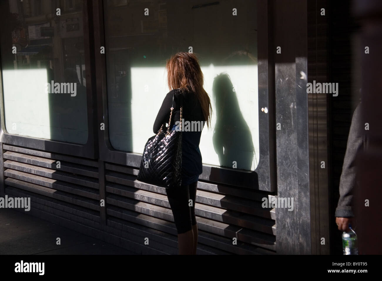 Back view of a woman in a London street with shadow; a man in an overcoat passes by - Stock Image