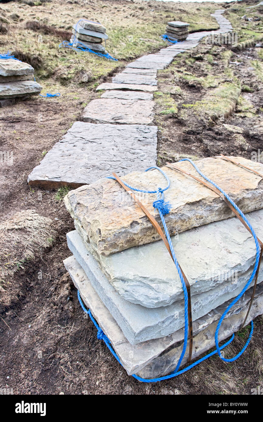 Slate block stone path being laid over peat moor to reduce erosion on the Pennine Way near Edale Derbyshire Peak - Stock Image
