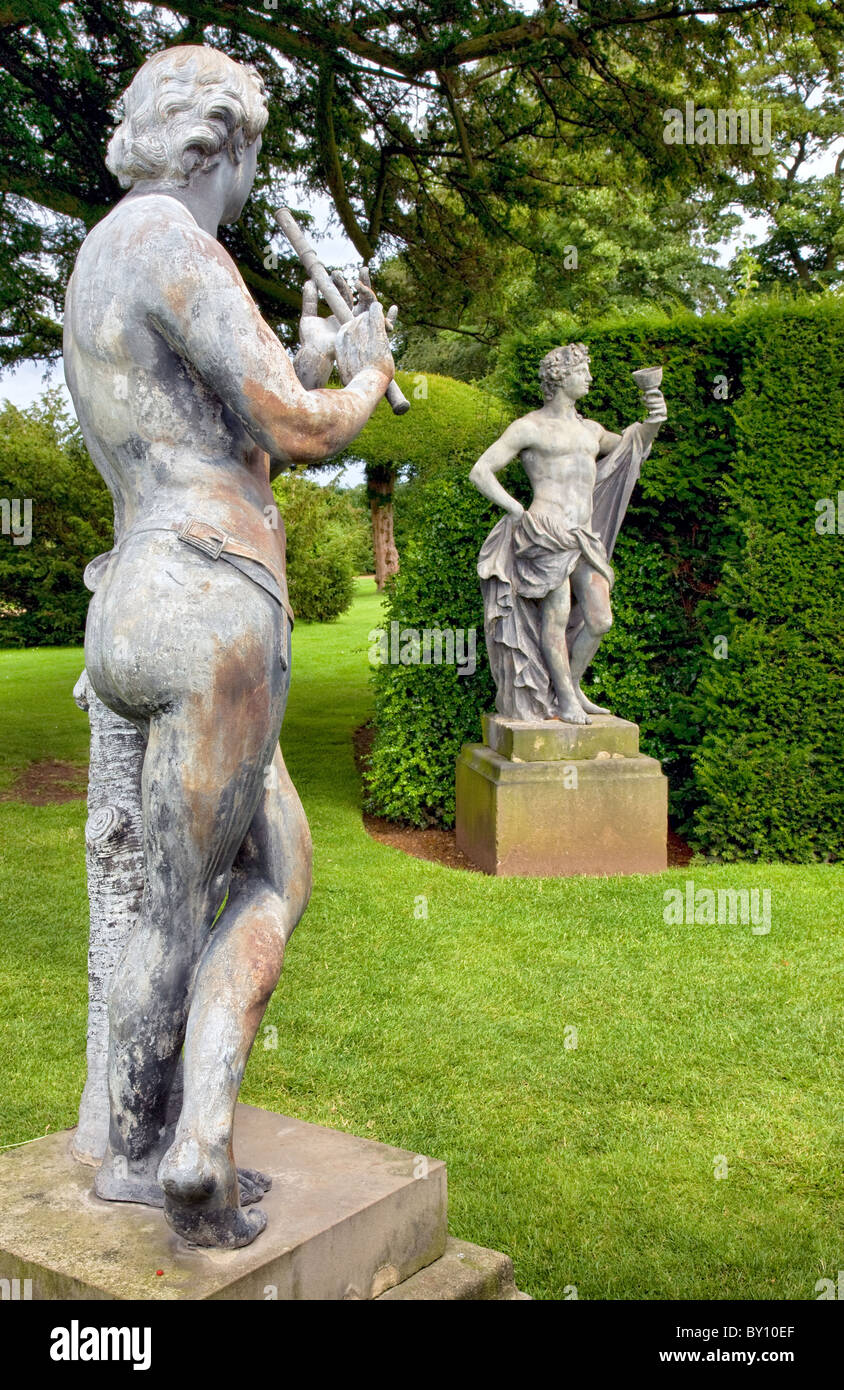 Lead garden sculptures of a barely clad flute player and Bacchus drinking from a goblet flank the yew walk at Hardwick - Stock Image
