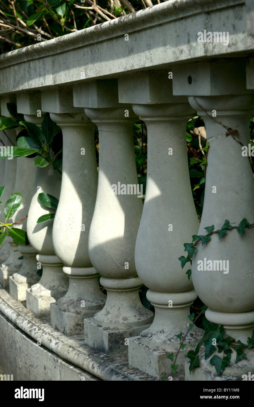 A row of stone balusters form a traditional balustrade to a bridge linking sections of a garden in the New Forest - Stock Image
