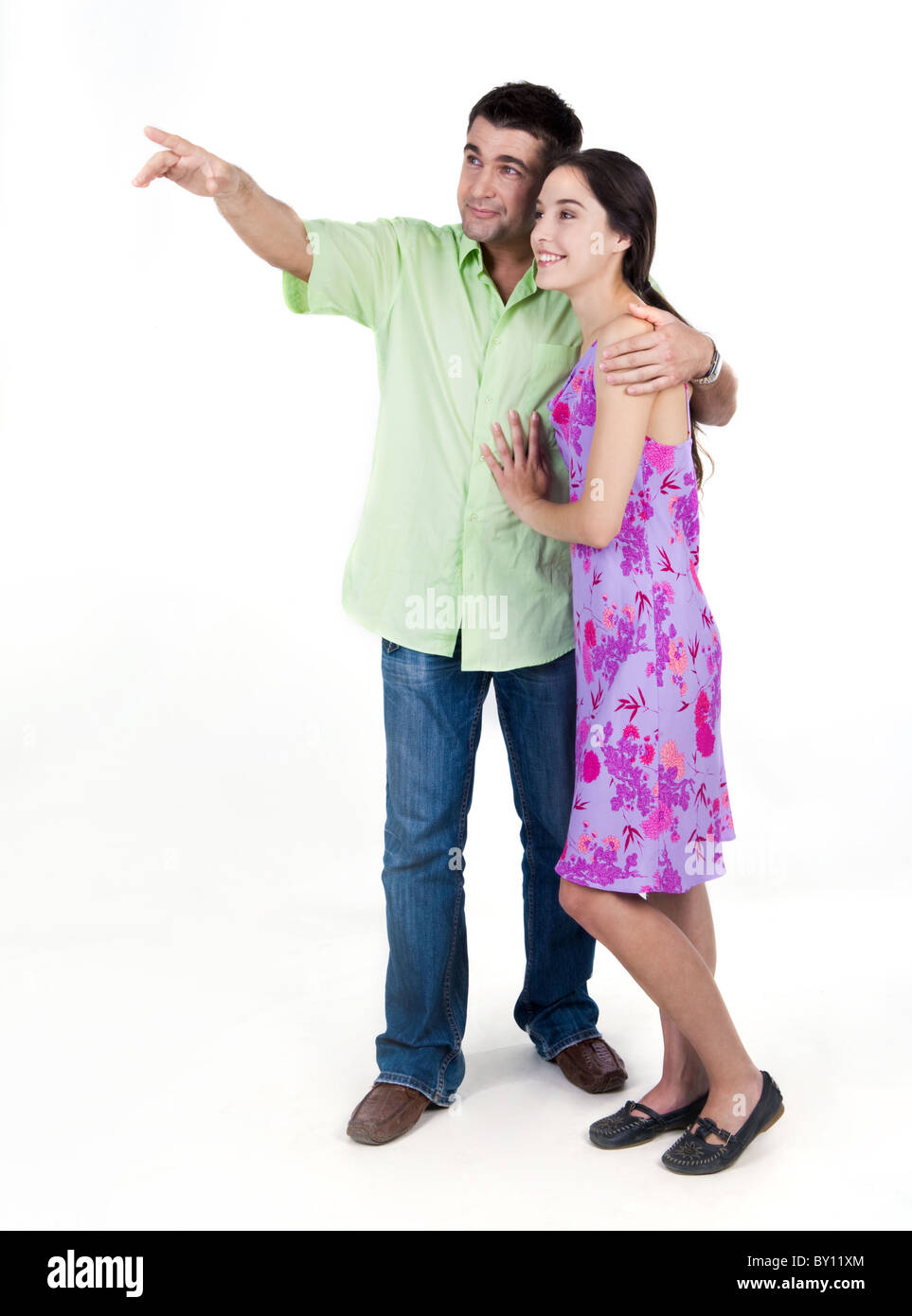 Portrait of young couple looking at something pointed at by man - Stock Image