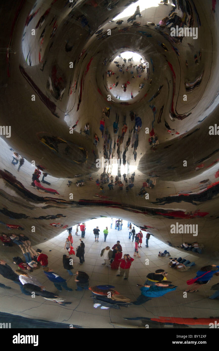 Visitors look at their reflection in the Cloud Gate sculpture located at the AT&T Plaza in Millennium Park, - Stock Image