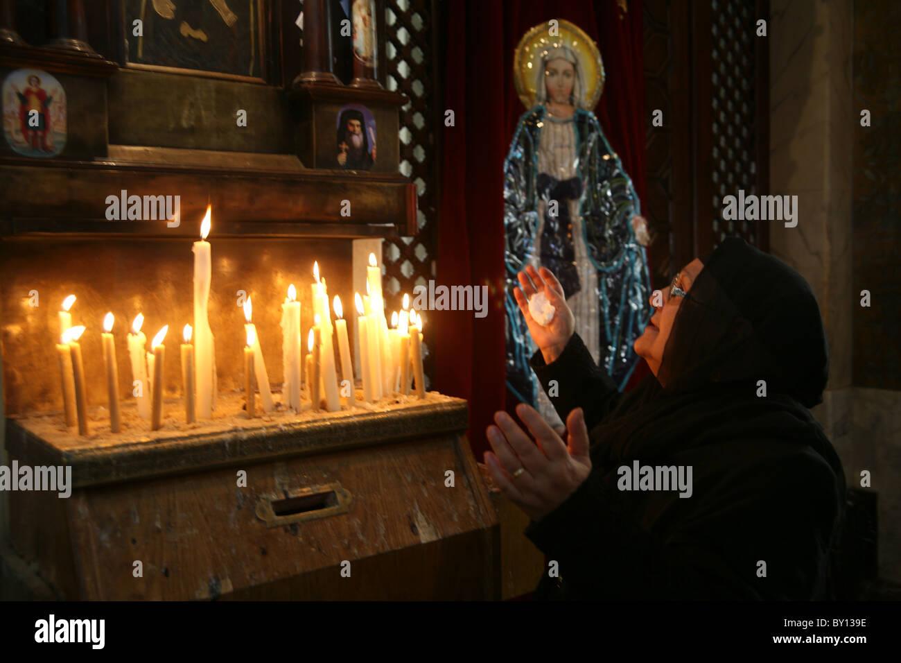 Old Egyptian lady prays in the Zeitoun Coptic Christian church in Cairo Egypt - Stock Image