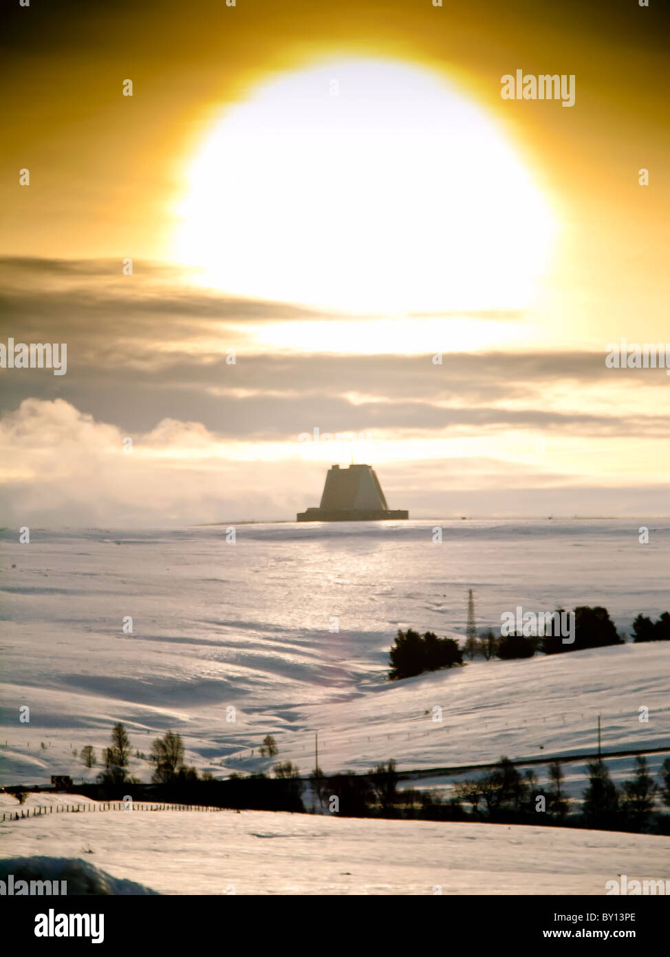 RAF Flylingdales early warning station in snow, North Yorkshire with setting sun looking bit like a nuclear explosion - Stock Image