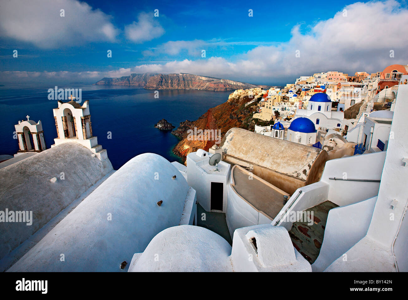 Santorini island, wide angle view of picturesque Oia village, hanging over the caldera. In the background, Thirasia - Stock Image