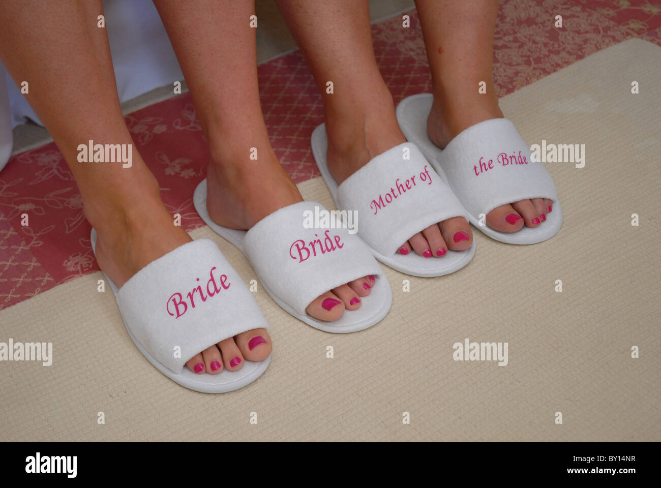 f477ff12df37 Bride and mother of the Bride wearing labeled slippers on the wedding  morning.