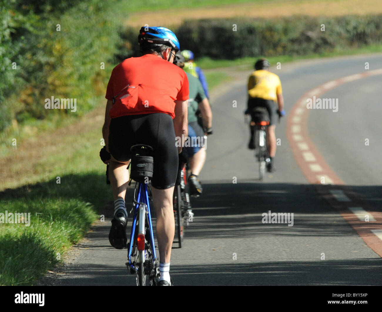 Brightly coloured cyclists cycling in the countryside. - Stock Image