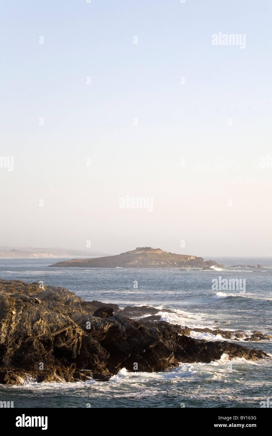 Pessegueiro Island seen from the rocky coastline of Porto Covo on Portugal's Alentejo coast. - Stock Image