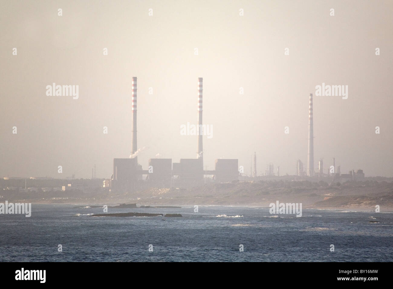 The chimneys of industrial plants at Sines on Portugal's Alentejo coast. - Stock Image