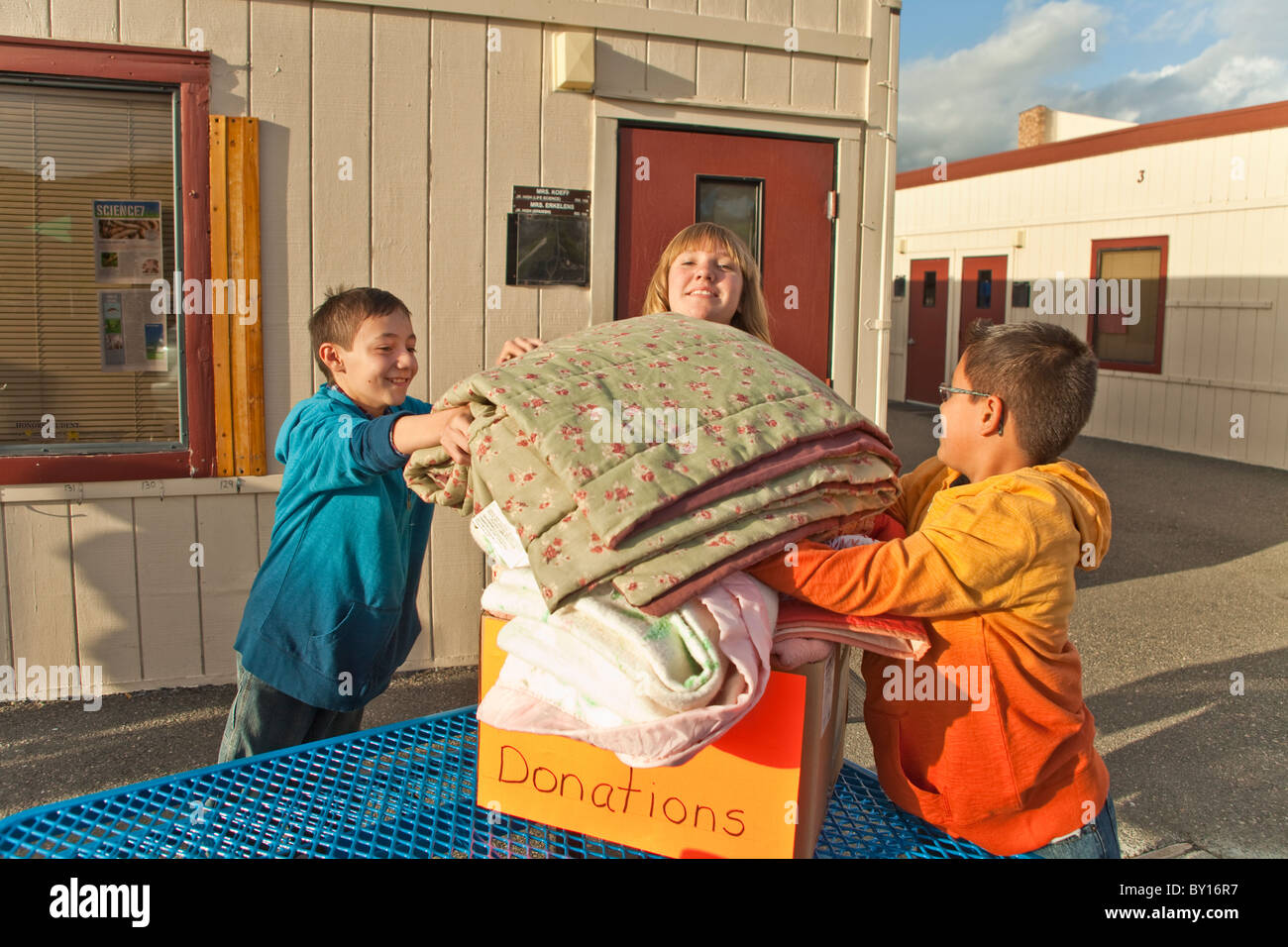 Middle school kids age 11-12 year old years collect blankets for people that are less fortunate child children helping - Stock Image