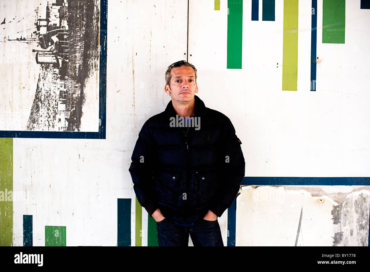 b7992cb62721c man in his 40s in urban scene leaning against wall with hands in pockets wearing  casual trendy clothes