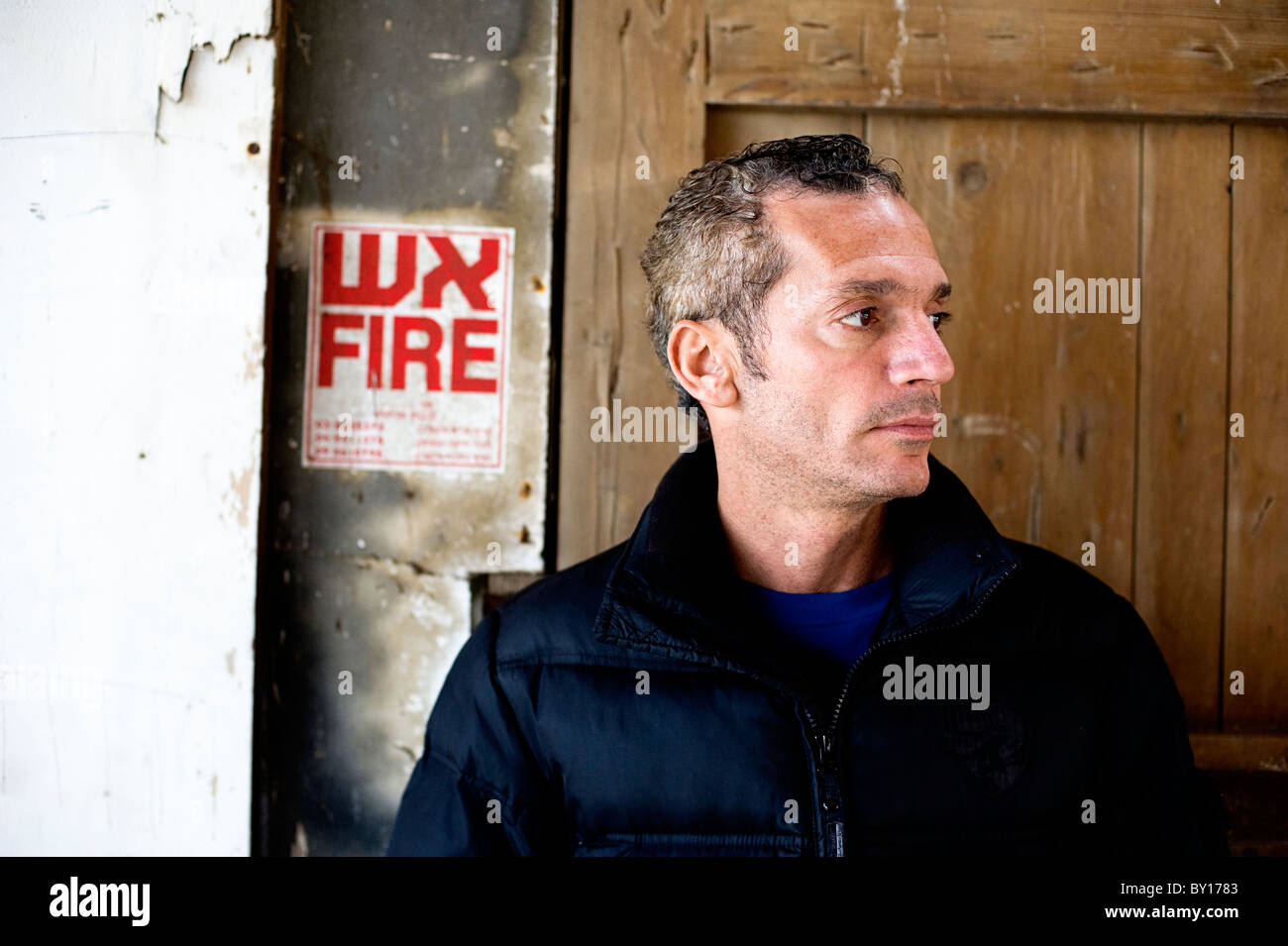 2ac2fee96de8d Man in his 40s in urban location wearing trendy casual clothes and standing  in front of an old door