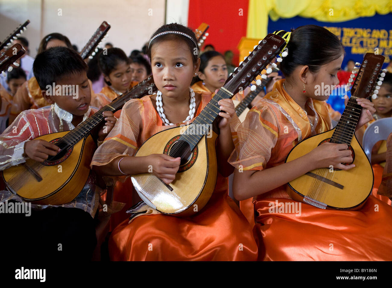 Filipino children play guitars during an event in Mansalay, Oriental Mindoro, Philippines. - Stock Image