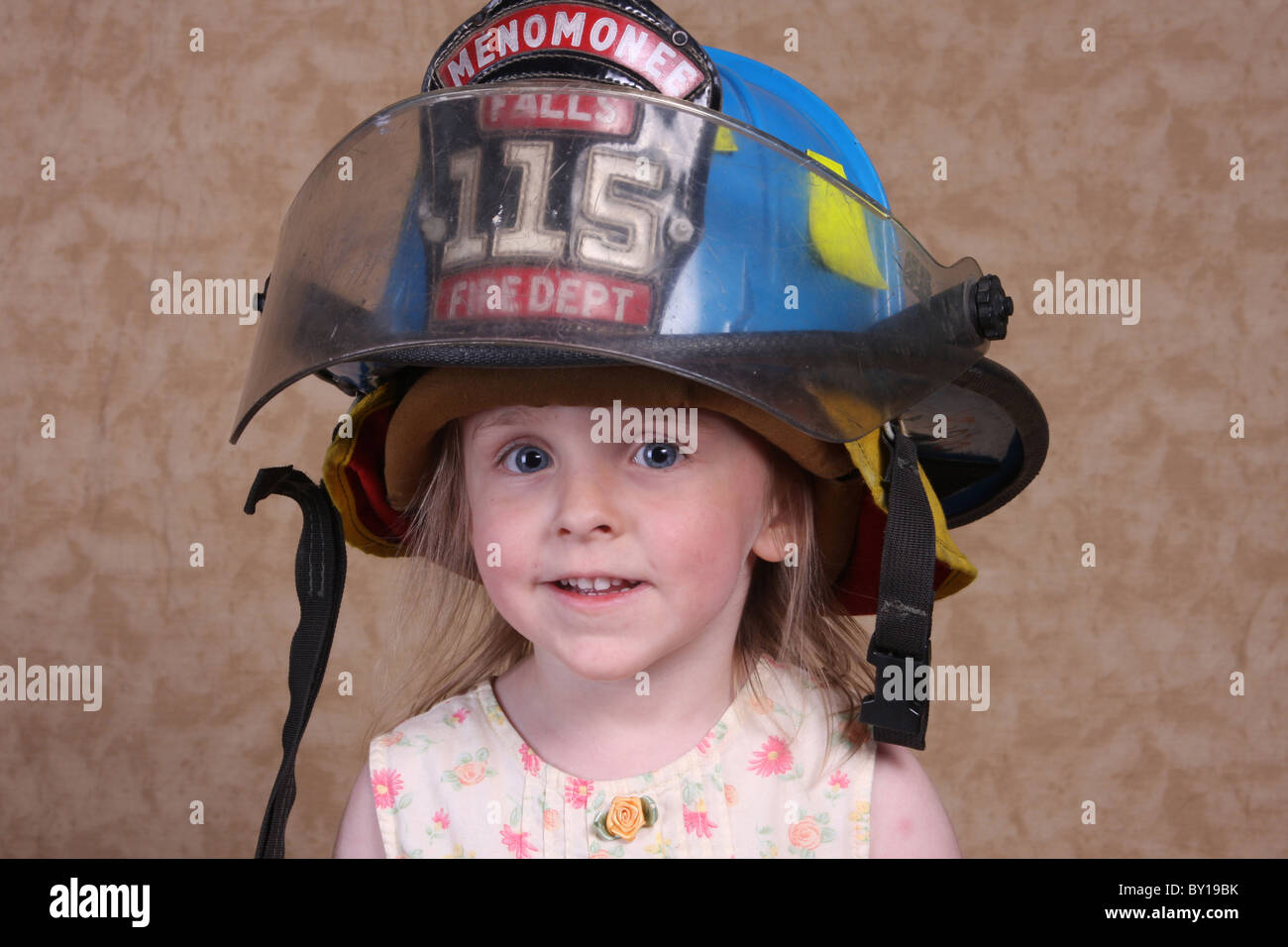 A young girl wearing her fathers firefighting helmet who is a member of the volunteer fire department - Stock Image