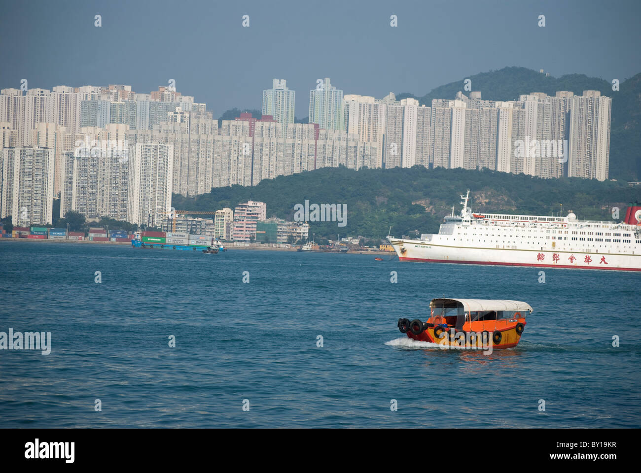 Red Sampan boat in the inland waters of Hong Kong and high buildings - Stock Image