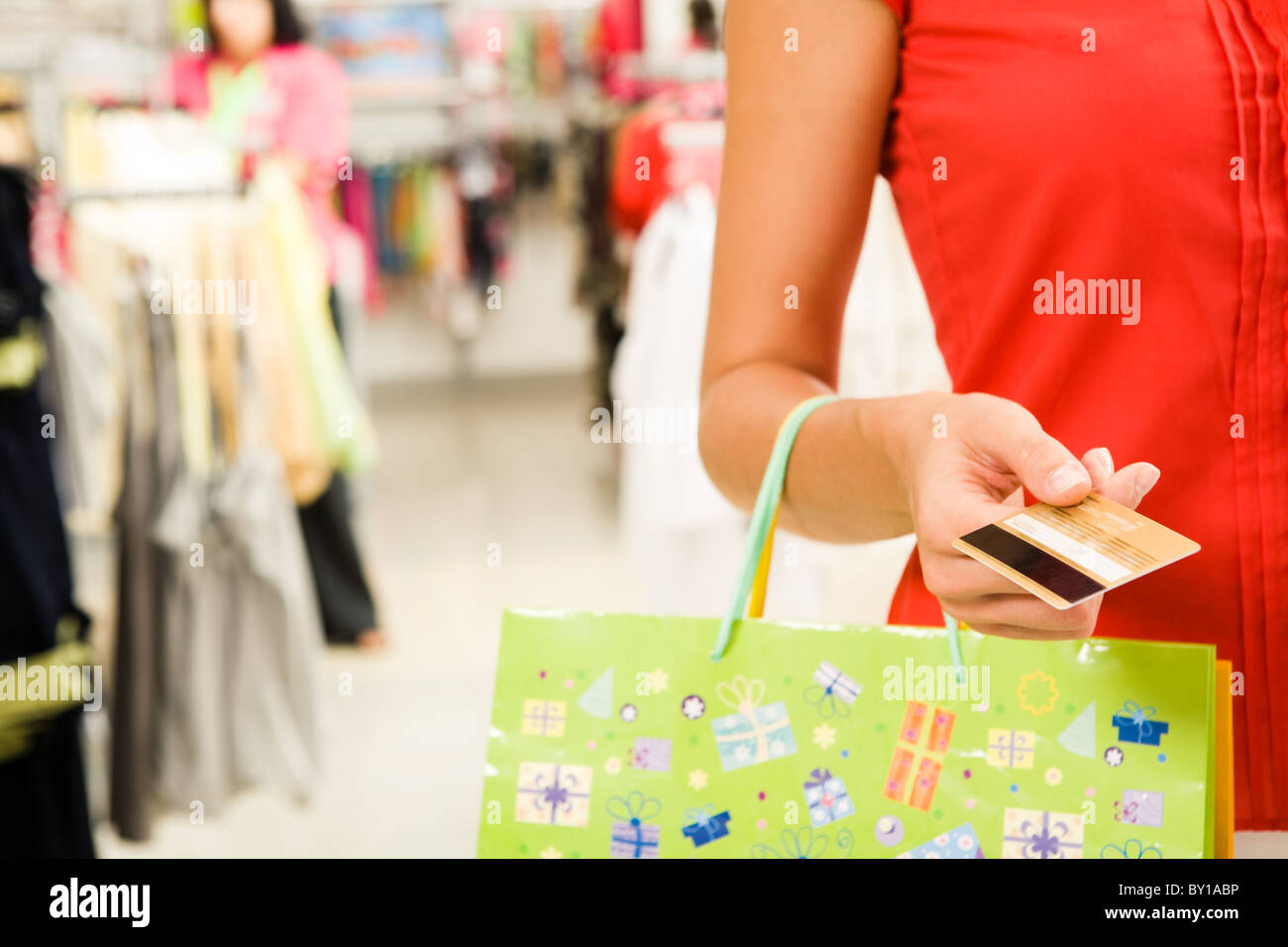 Close-up of woman's hand holding plastic card while going shopping in the mall - Stock Image