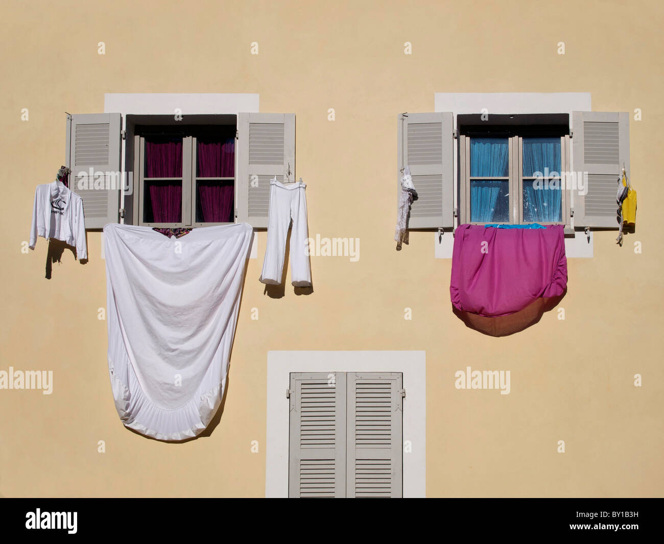 Bed sheets and clothes drying hanging from the windows of a house in a street in southern France - Stock Image