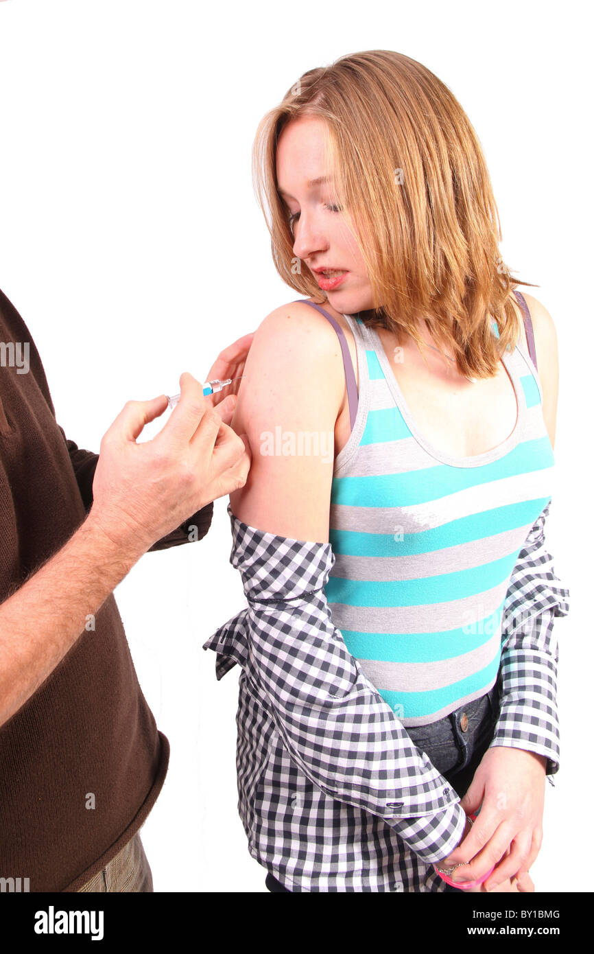 Doctor giving a vaccination in arm of young woman - Stock Image
