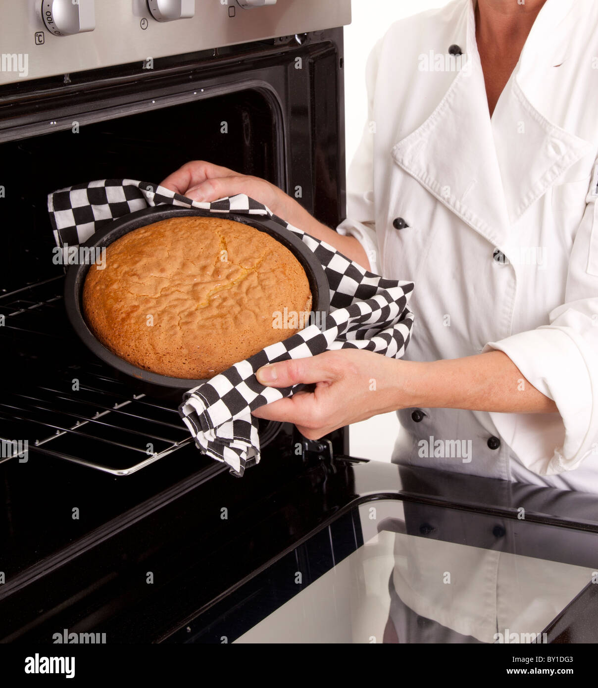 CHEF TAKING COOKED SPONGE CAKE OUT OF OVEN - Stock Image