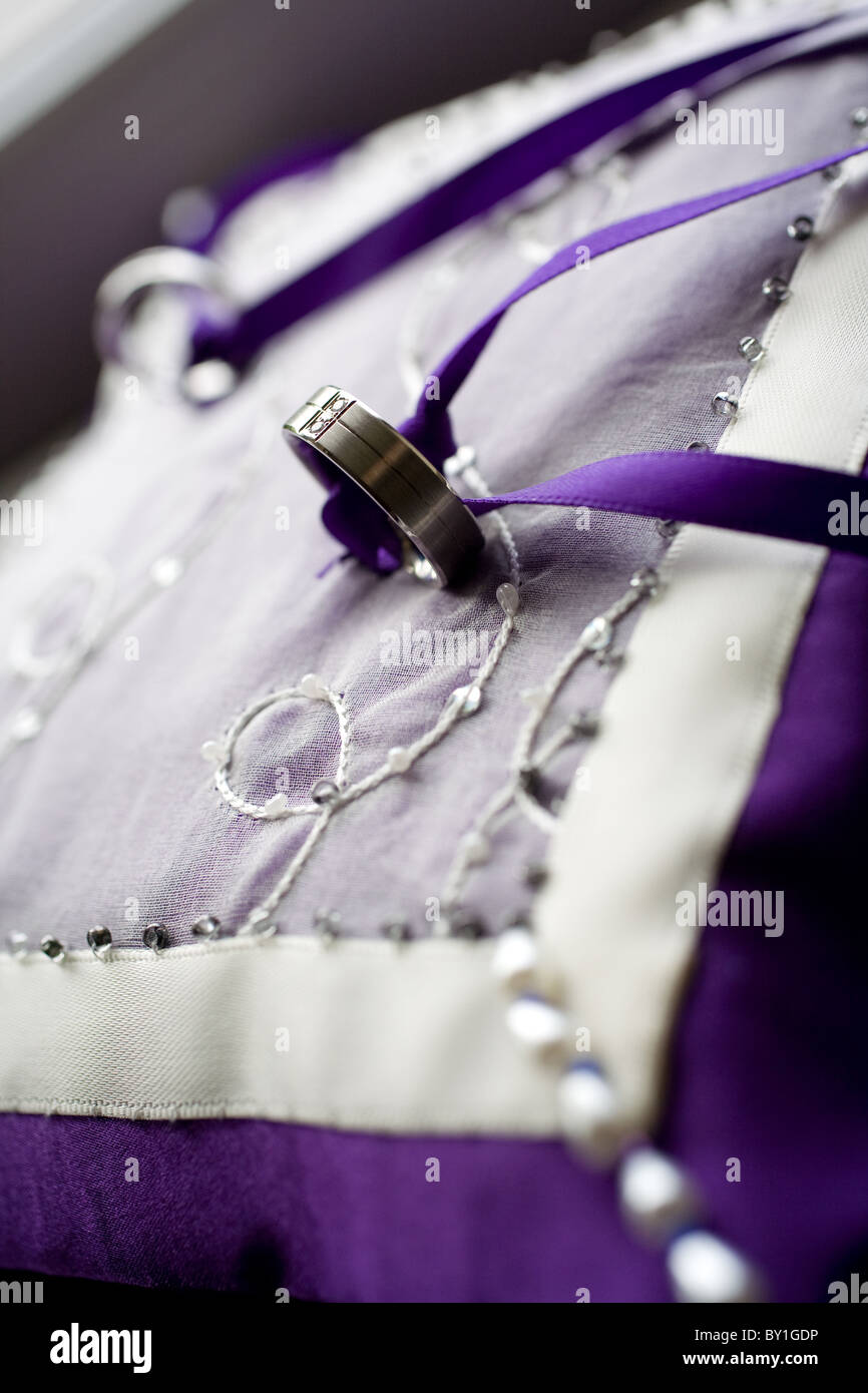 Purple beaded ring cushion with bride and groom rings attached - Stock Image