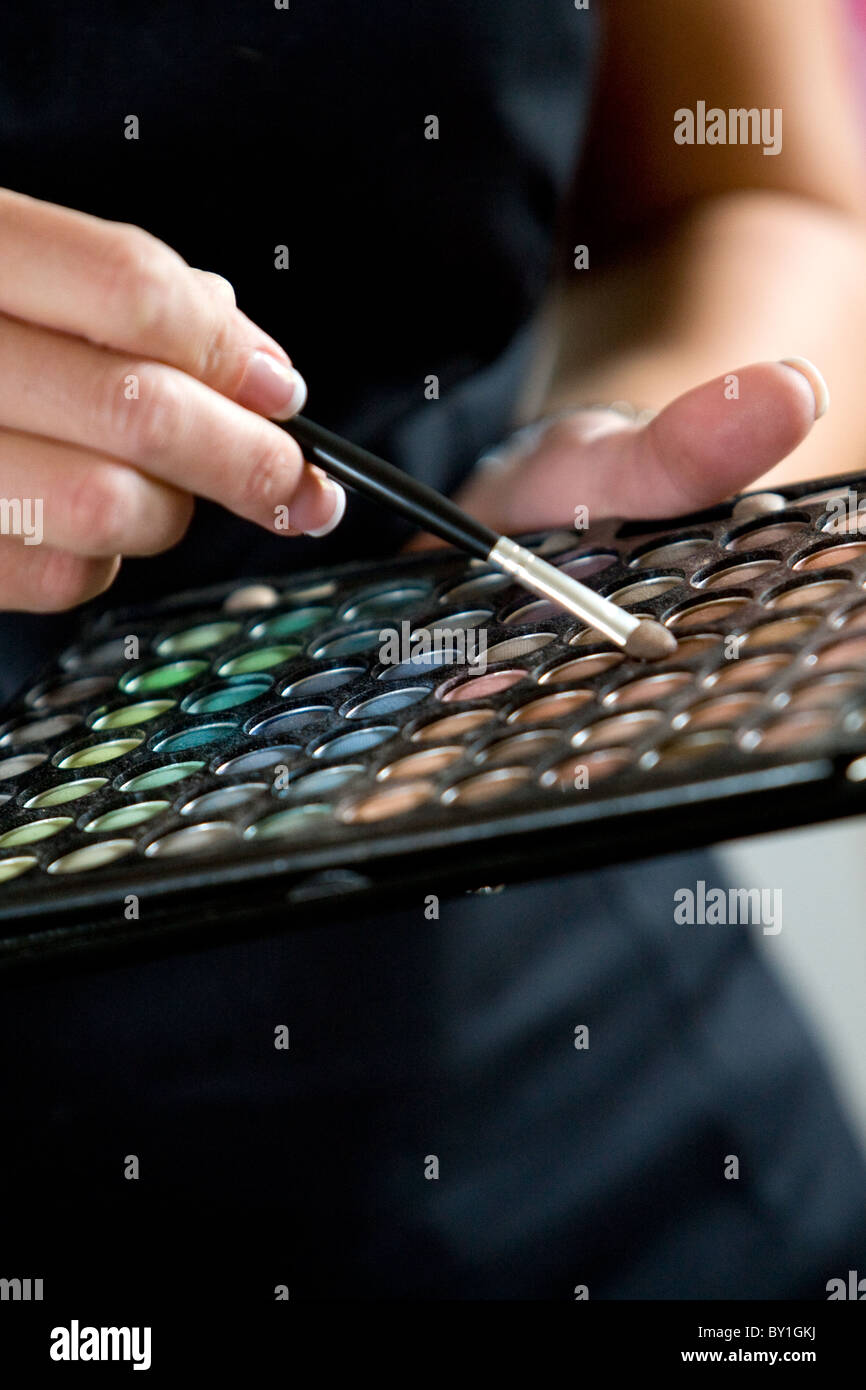 Make up artist holding eye shadow palette and brush - Stock Image
