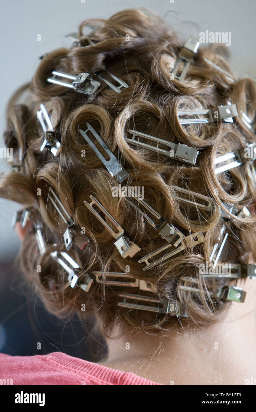 blonde bridesmaid hair in curlers and grips - Stock Image