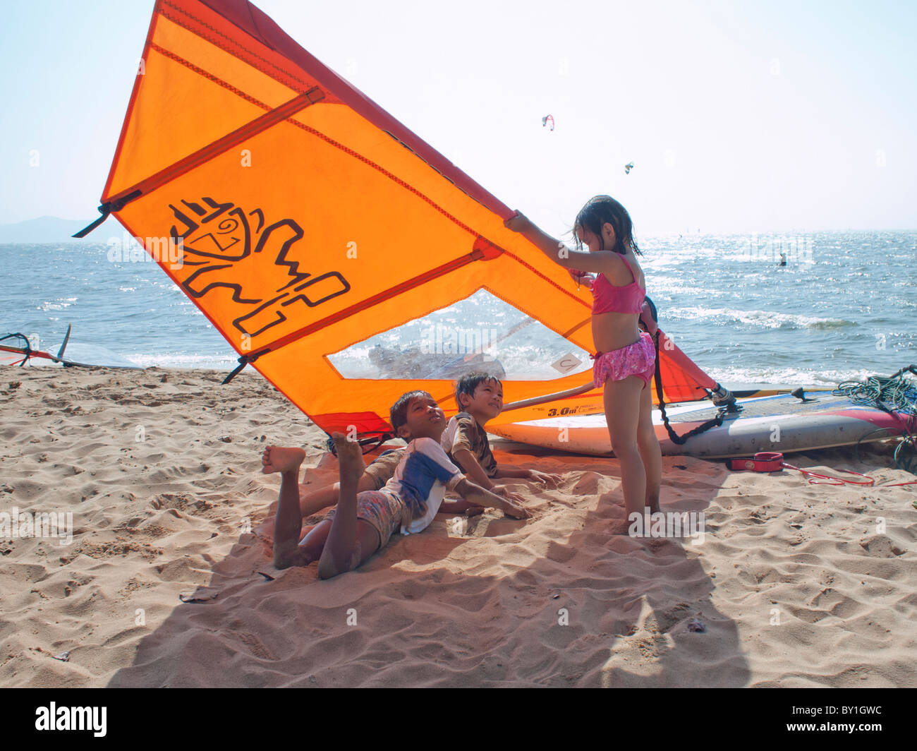 A kids playing hide and seek on the beach - Stock Image