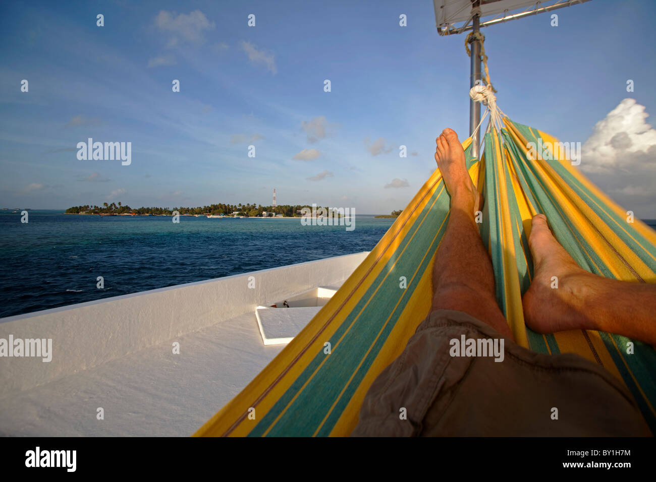 Relaxing in a hammock overlooking a coral attol in the South Ari Attol group of islands, Maldives - Stock Image