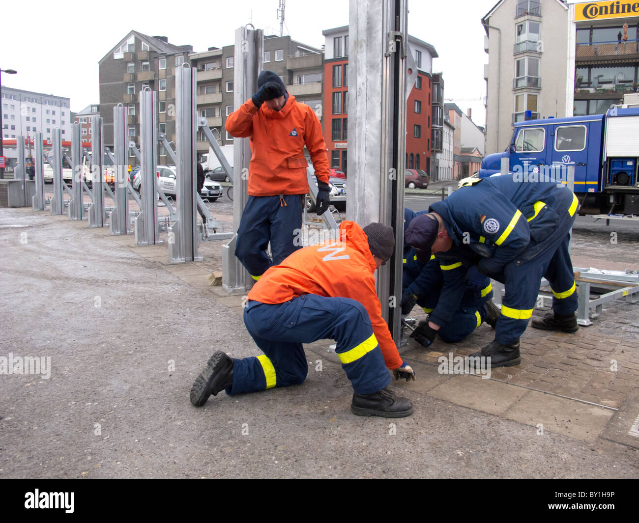 Installing flood defence barriers beside River Rheine in central Cologne during flooding conditions Germany - Stock Image