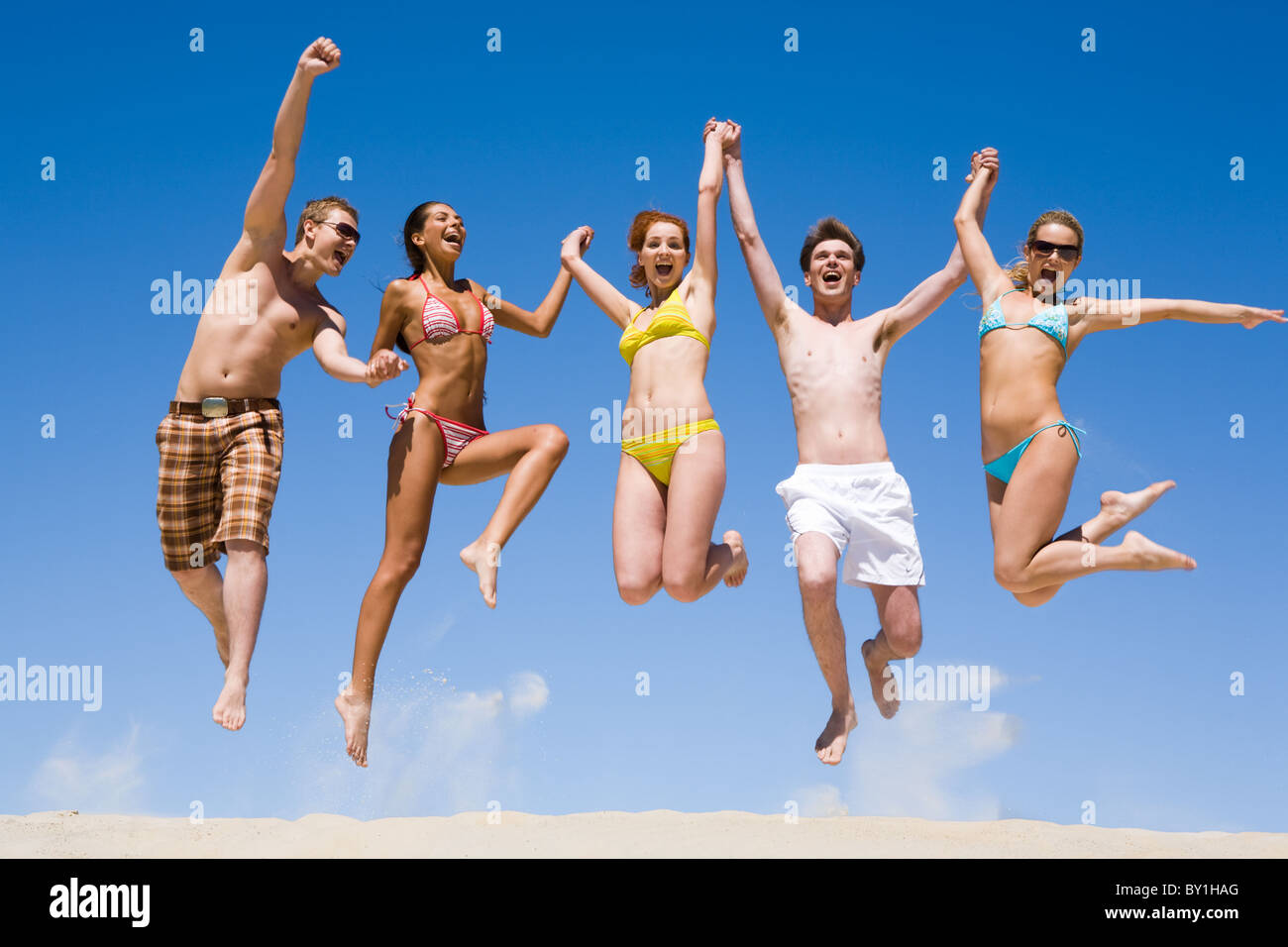 Joyful team of friends holding for hands each other and jumping - Stock Image